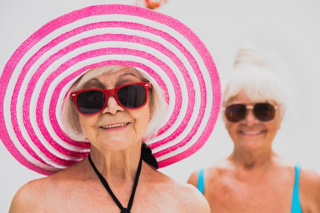 Happy senior women having party in the swimming pool - elderly friends relaxing at a pool party