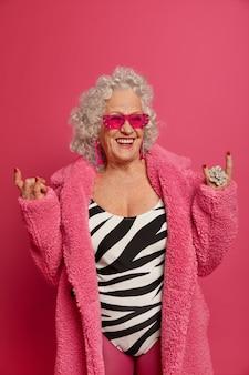 행복한 노인 주름진 여자는 바위 기호를하고 최신 패션 트렌드를 착용합니다.