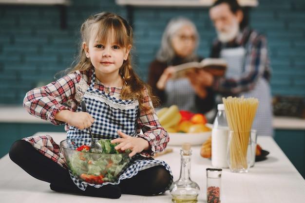 幸せな先輩とその孫娘がキッチンで料理をする