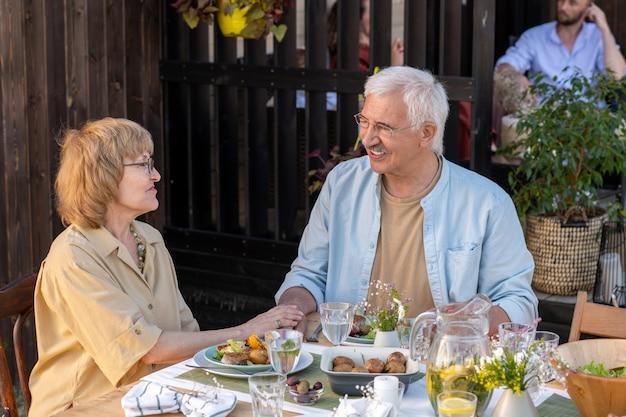 Счастливые пожилые люди обсуждают свою семейную жизнь после ужина в выходные