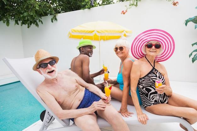 スイミングプールでパーティーをしている幸せな先輩夏の間のプールパーティーで年配の友人