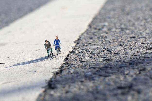 Миниатюра счастливых пожилых людей на велосипедной прогулке по проселочной дороге в солнечный день.