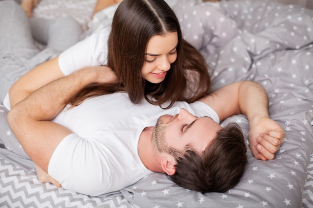 Happy sensual young couple lying in bed together.