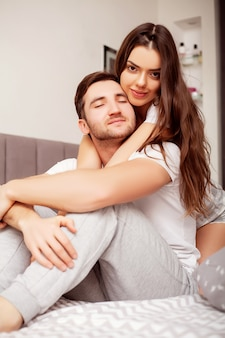 Happy sensual young couple lying in bed together