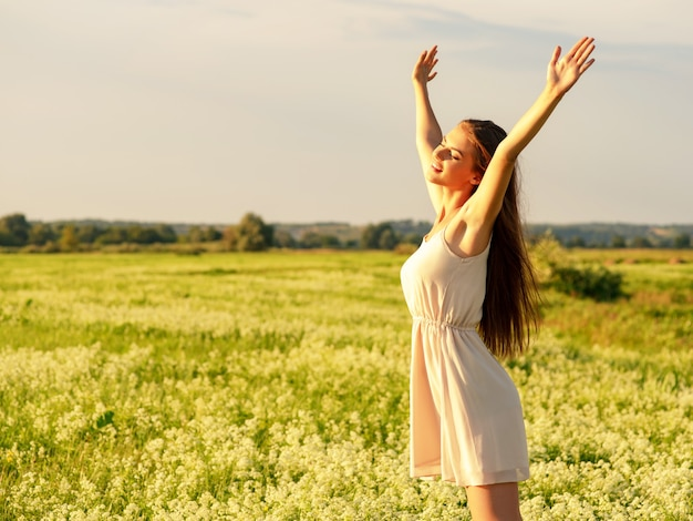 Happy  and serene behavior woman  outdoor with raised hands young cheerful girl is on nature over the spring field happiness  peoplepretty and joyful  model is relaxing on the meadow