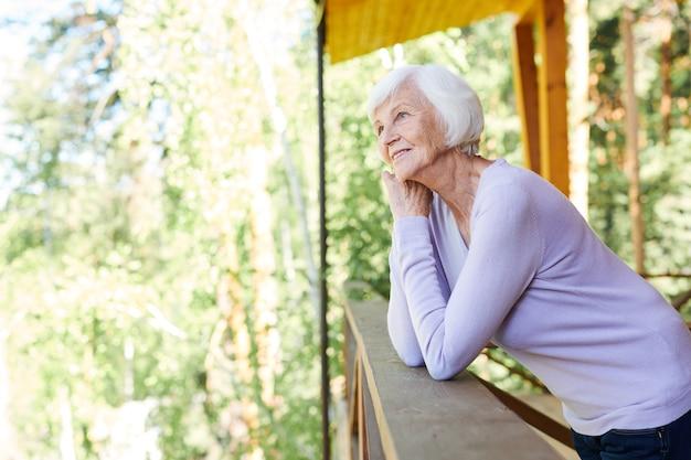 나무 난간에 서있는 동안 시골집에서 휴식을 즐기는 캐주얼웨어에 행복 고요한 수석 여성