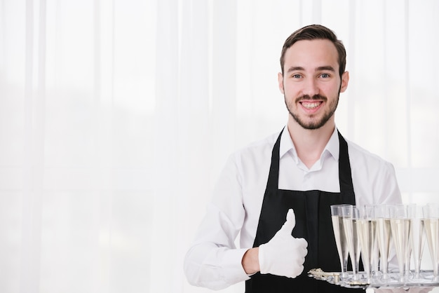 Happy servant carrying champagne glasses with copy space