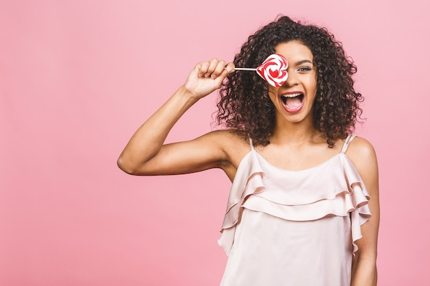 막대 사탕을 먹는 행복 섹시 미국 아프리카 소녀. 분홍색 배경에 고립 된 분홍색 달콤한 다채로운 롤리팝 사탕을 들고 아름다움 매력적인 모델 여자. 과자.