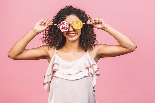ロリポップを食べる幸せなセクシーなアメリカのアフロの女の子。ピンクの背景に分離されたピンクの甘いカラフルなロリポップキャンディーを保持している美容グラマーモデルの女性。お菓子。