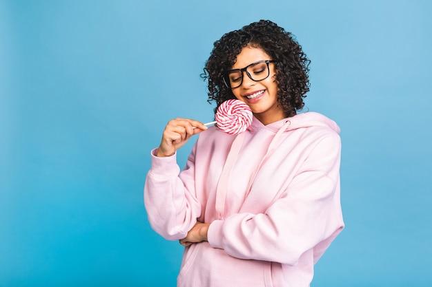 ロリポップを食べる幸せなセクシーなアメリカのアフロの女の子。青い背景で隔離の甘いカラフルなロリポップキャンディーを保持している美容グラマーモデルの女性。お菓子。
