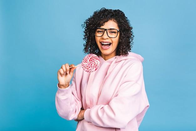 막대 사탕을 먹는 행복 섹시 미국 아프리카 소녀. 파란색 배경에 고립 된 달콤한 다채로운 롤리팝 사탕을 들고 아름다움 매력적인 모델 여자. 과자.
