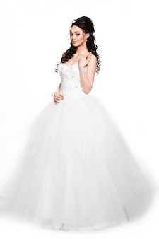 Счастливая сексуальная красивая невеста брюнетка девушка в белом свадебном платье с прической и ярким макияжем на белом фоне