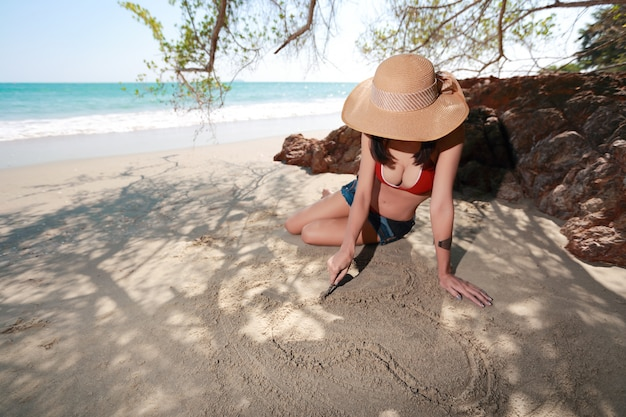 Happy and sexy woman with hat drawing heart symbol on sandy beach