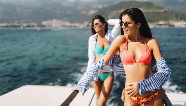 Счастливые сексуальные женщины-друзья наслаждаются летними каникулами на пляже