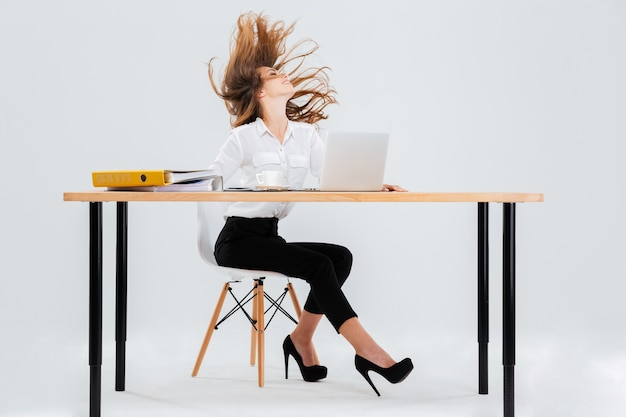 Happy sexy young businesswoman sitting at the table with hair flying in the air over white background
