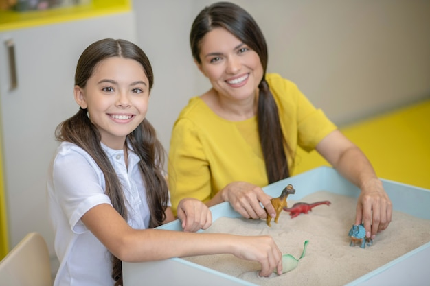 Happy shining long-haired girl and smiling woman psychologist with miniature animal figurines near sand tray