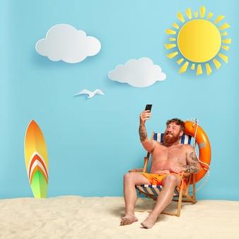 Счастливый бородатый рыжий мужчина без рубашки позирует на пляже