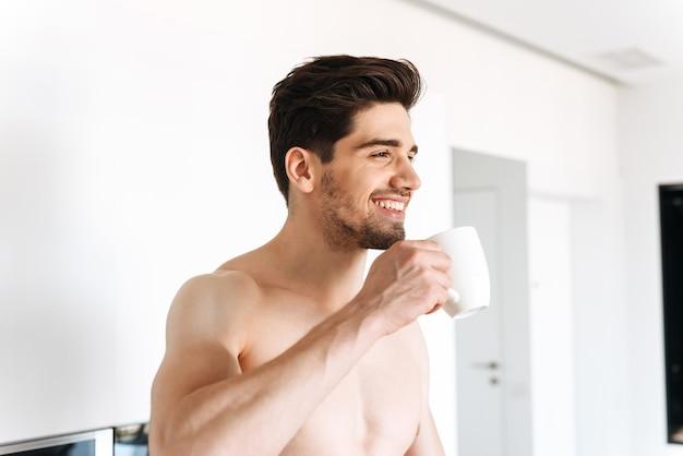 Счастливый мужчина без рубашки пьет кофе