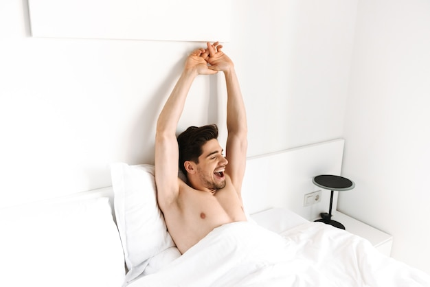 Happy shirtless man stretching his hands while laying