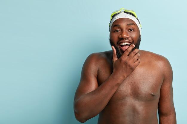 어두운 피부를 가진 행복한 벗은 남자는 수영, 레크리에이션 시간 및 피트니스를 즐기고 턱을 잡고 긍정적으로 시선을 보냅니다.