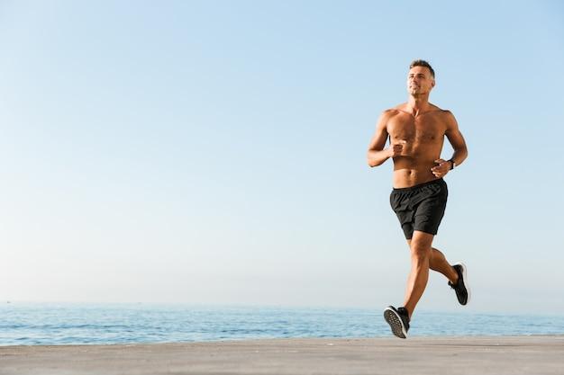 走っている幸せな上半身裸のスポーツマン