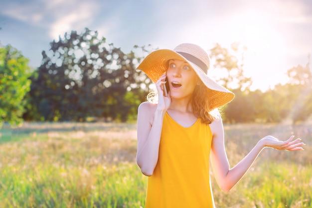 夏の帽子で幸せなショックを受けた女性女性とスマートフォン、緑豊かな公園の屋外で携帯電話で話す明るい黄色の夏のドレス。夏、春のアクティブなアウトドアレジャーのコンセプト。