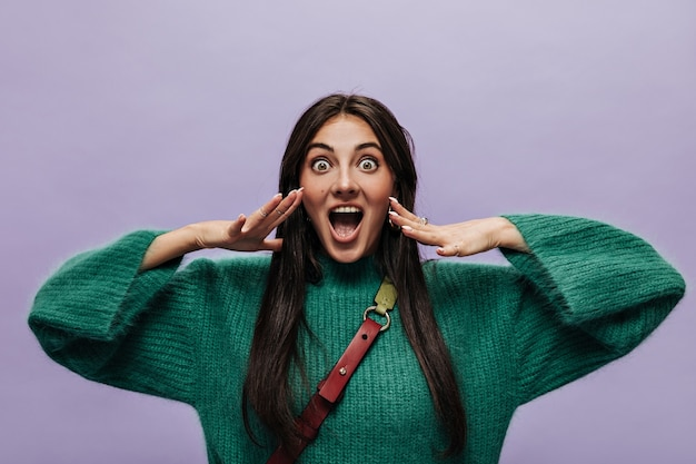 Happy shocked woman in green knitted sweater looks into camera