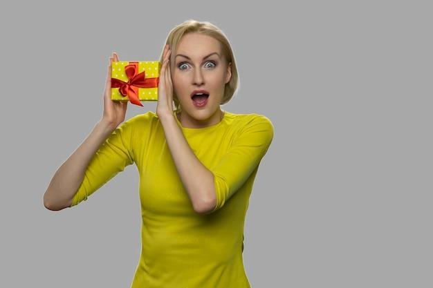 선물 상자를 들고 행복 충격 된 여자입니다. 회색 배경에 선물 상자와 함께 포즈를 취하는 흥분된 백인 여자.