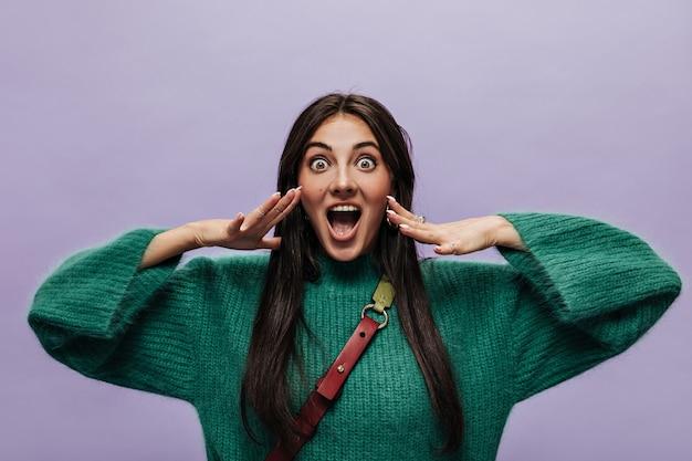 緑のニットセーターで幸せなショックを受けた女性がカメラをのぞきます