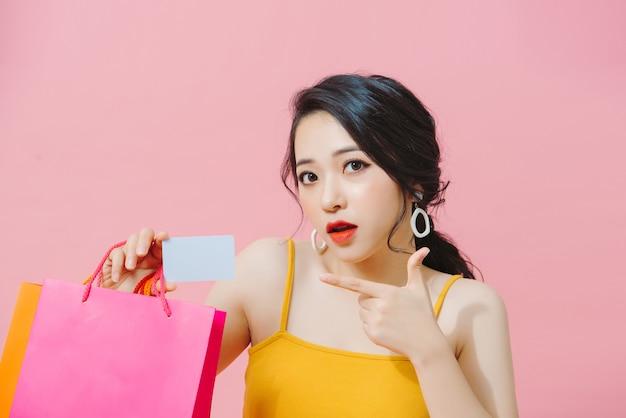 ハッピーショパホリック。カラフルなショッピングバッグとピンクの背景で隔離のクレジットカードを持つうれしそうなアジアの女の子の肖像画