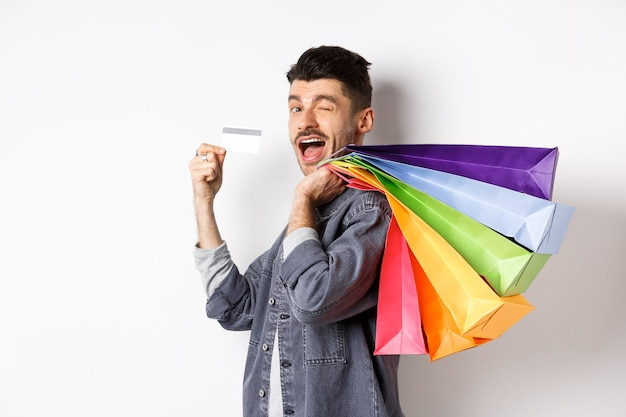 Happy shopper holding shopping bags over shoulder and showing plastic credit card, paying contactless, standing on white background.