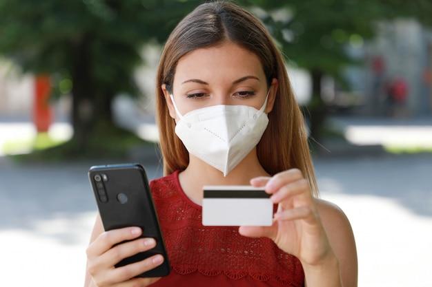 Ffp2マスクで幸せな買い物客の女性が路上でスマートフォンとクレジットカードでオンラインで購入