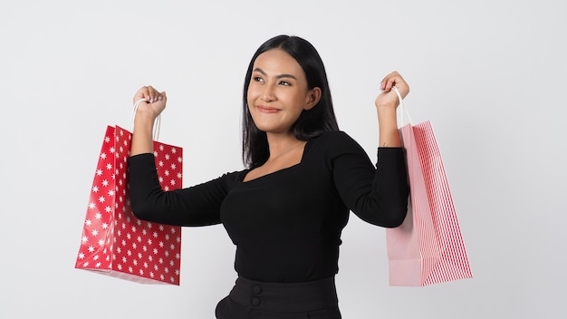 Happy shopping concept. young asian thai woman in action or activity of purchasing goods from stores or online shop. happily girl and shopping bags during sale season in studio white background