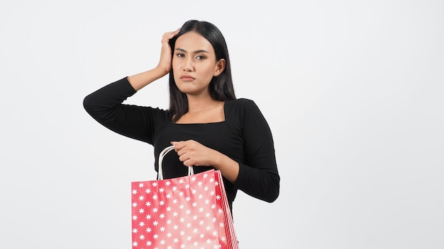 행복 한 쇼핑 개념입니다. 상점이나 온라인 상점에서 물건을 구매하는 행동 또는 활동에 젊은 아시아 태국 여성. 행복하게 소녀와 스튜디오 흰색 배경에서 판매 시즌 동안 쇼핑 가방