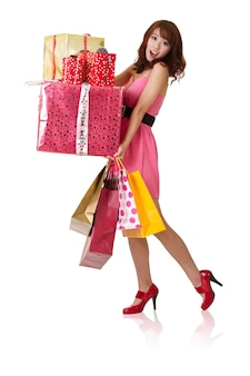 バッグとギフトボックス、白い壁に分離された全身像を保持している幸せなショッピングの女の子。