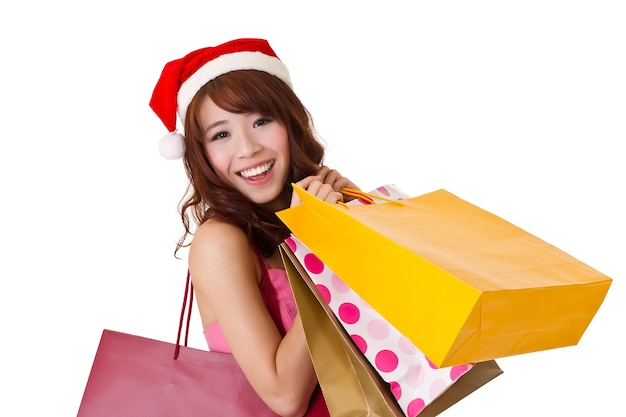 Happy shopping girl holding bags and wearing christmas hat, half length closeup portrait on white wall.