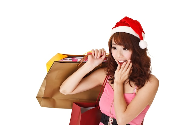 Happy shopping girl holding bags and wearing christmas hat with surprised expression, half length closeup portrait on white wall.