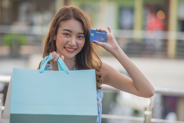 Happy shopping time concept, young asian woman with shopping bags and holding credit card in hand at mall.