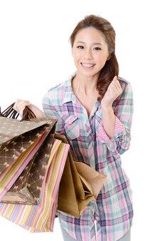 バッグを保持しているアジアの幸せな買い物の女性