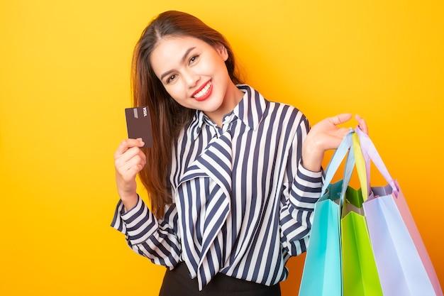 Счастливая женщина с покупками на желтом фоне