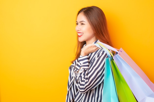 Happy shopping woman on yellow background