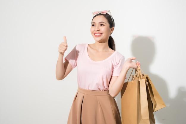 幸せな買い物の若い女性はバッグで親指を表示-孤立した、アジアのモデル