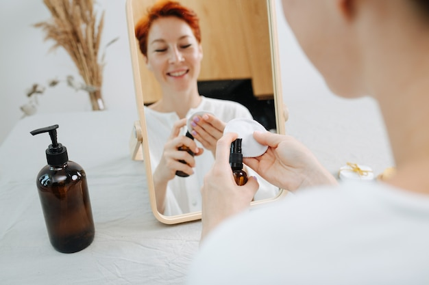 Счастливая короткошерстная женщина сидит перед зеркалом, применяя мицеллярную воду. использование экологически чистых продуктов и вещей.