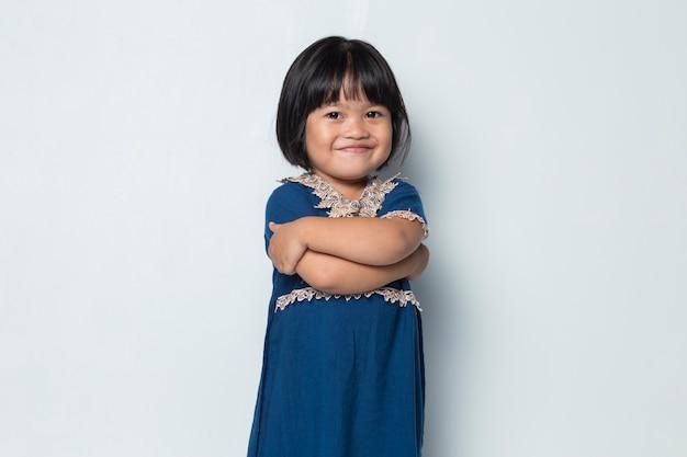 팔짱을 끼고 행복한 수줍은 아시아 소녀 미소