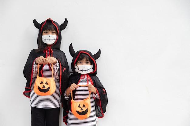 할로윈 파티에서 행복한 남매 소녀들. 할로윈 의상을 입은 아이들. 파티 준비가 된 아이들의 개념.