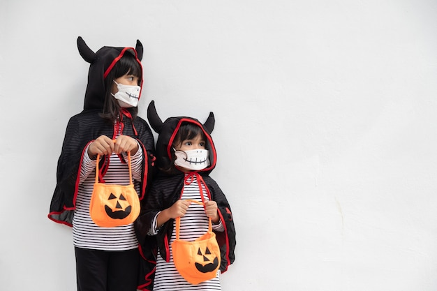 Happy sibling girls at the halloween party. children wearing costumes halloweens. concept of children ready for a party.