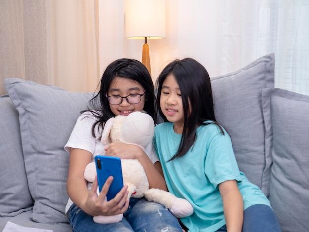 リビングのソファに座っている幸せな兄弟の子供たちが携帯電話で親と一緒に話し、スマートフォンでかわいい妹のビデオ通話を見せている笑顔の姉が家族と話します。