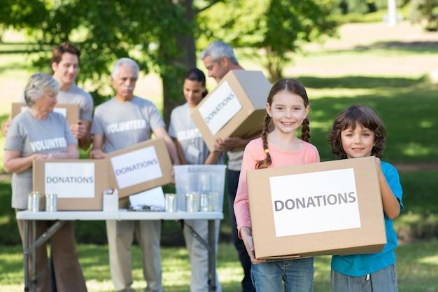 Счастливые братья и сестры, держащие пожертвование