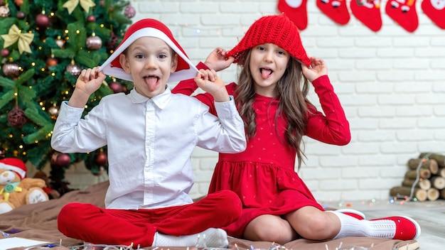 自宅のクリスマスツリーの近くの床にクリスマスの衣装で幸せな兄弟。幸せな家族のアイデア