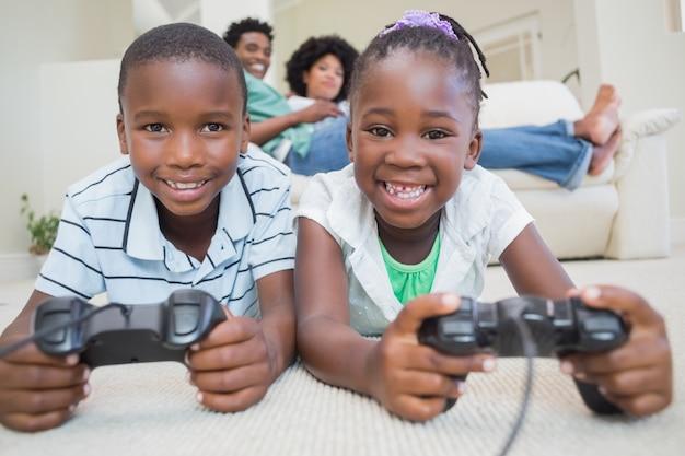 ビデオゲームをする床に横たわっている幸せな兄弟